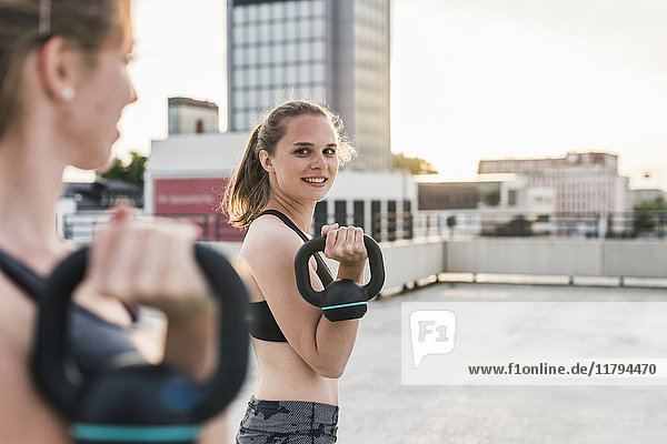 Two women exercising with kettlebells on parking level in the city