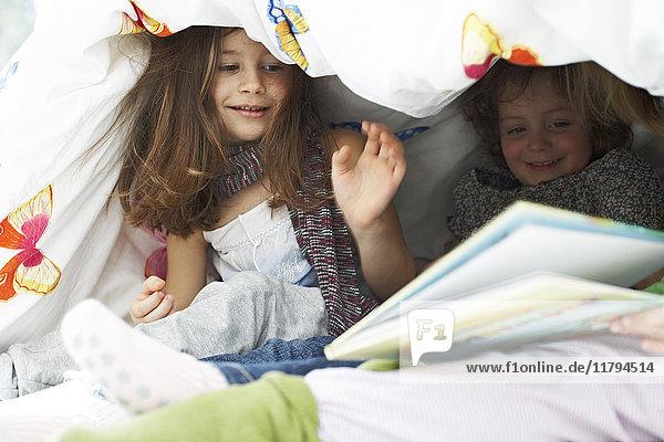Three little children with book together under blanket