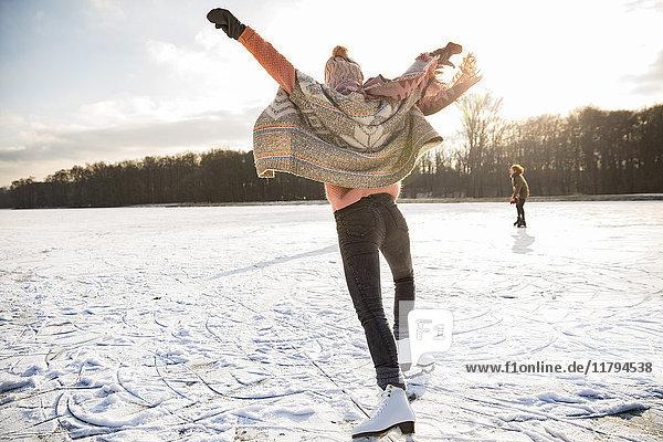 Rückansicht der Frau mit Schlittschuhen auf dem zugefrorenen See
