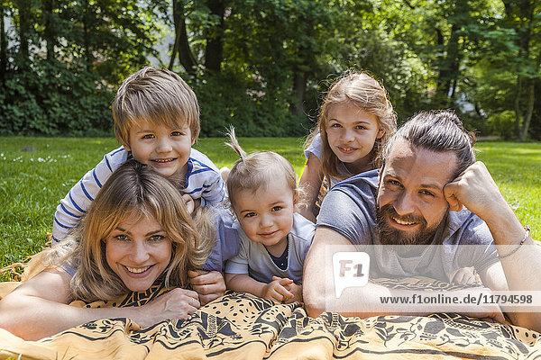 Porträt einer glücklichen Familie auf der Wiese liegend