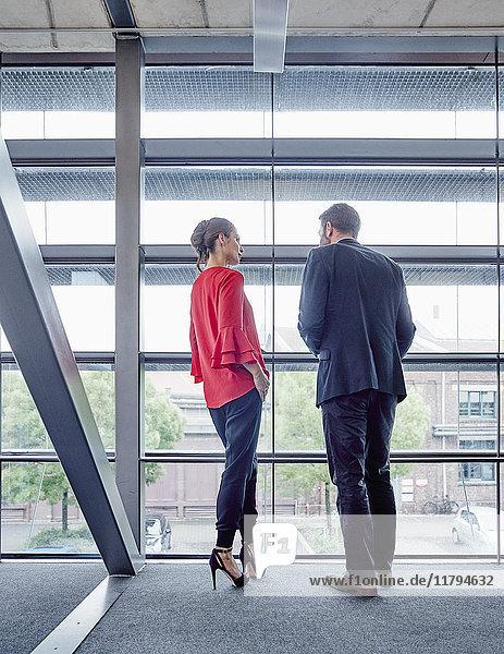 Geschäftsmann und Geschäftsfrau im Gespräch am Fenster