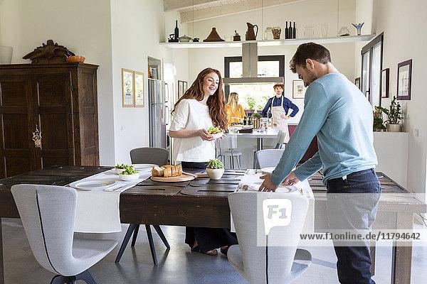 Zwei Paare kochen und decken gemeinsam den Tisch.