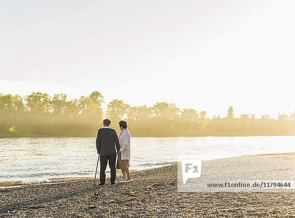 Senior couple standing on at riverside by sunset
