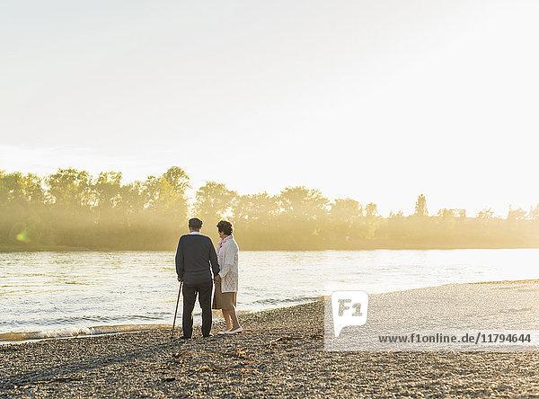 Seniorenpaar steht am Flussufer bei Sonnenuntergang