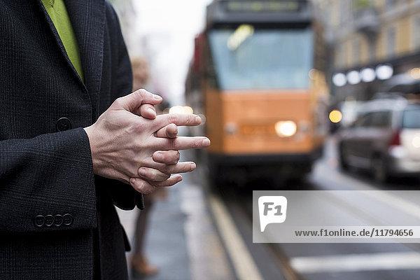 Nahaufnahme der gefalteten Hände des Geschäftsmannes in der Stadt an der Straßenbahnhaltestelle