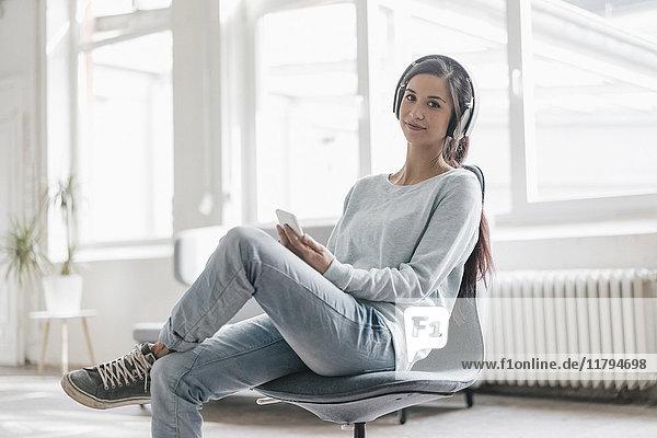 Junge Frau  die einen Videoanruf von ihrem Handy aus tätigt und Kopfhörer trägt