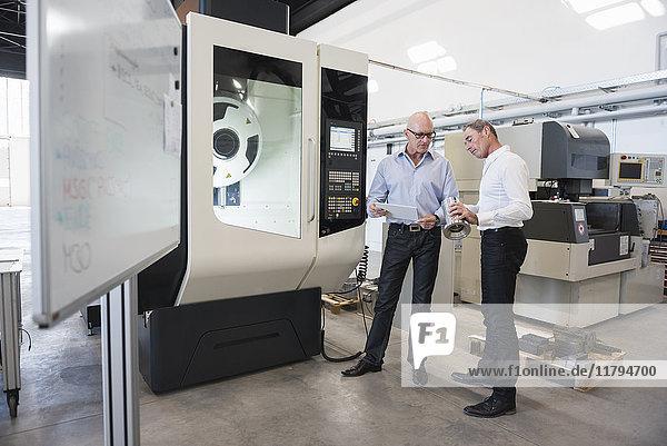 Zwei Männer betrachten Tablette und Produkt in der Fabrik