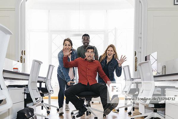 Mitarbeiter schieben ihren Chef auf einem Drehstuhl durchs Büro
