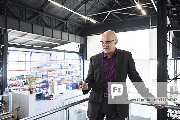 Geschäftsmann mit Handy in der Fabrikhalle