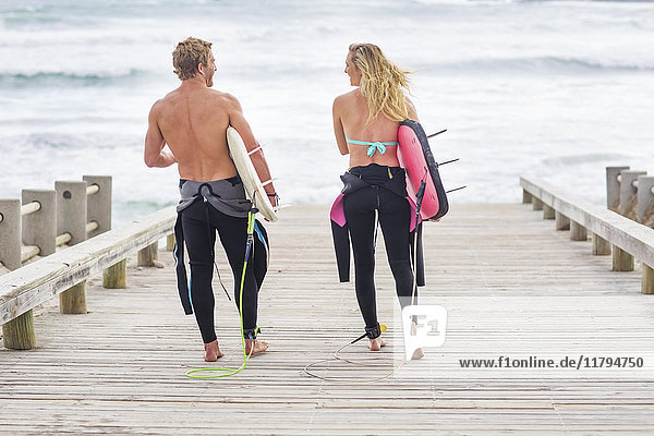 Paar Spaziergänge zum Strand mit Surfbrettern