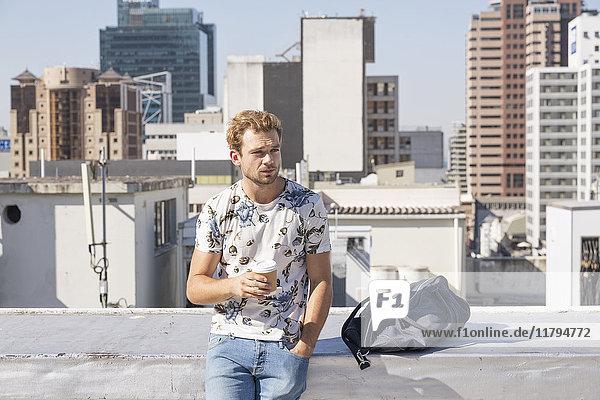 Junger Mann steht auf der Dachterrasse und trinkt Kaffee.