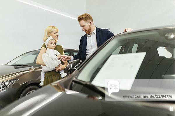 Familie im Autohaus bei der Wahl des Familienfahrzeuges