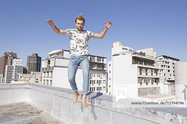 Barfüßiger Mann  der von der Balustrade einer Dachterrasse springt.