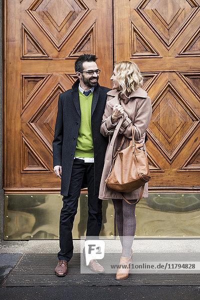Lächelnder Geschäftsmann und Geschäftsfrau vor einem Tor