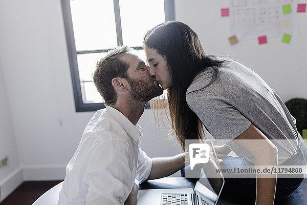 Glückliches Paar mit Laptop zu Hause küssen