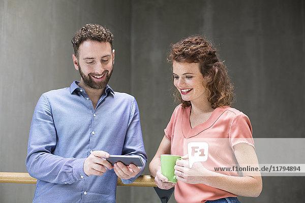Mann und Frau im Treppenhaus mit Handy und Tasse Kaffee
