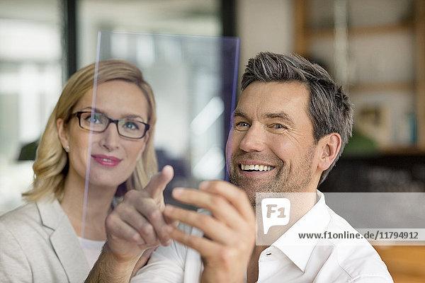 Lächelnder Geschäftsmann und Frau mit futuristischem tragbarem Gerät