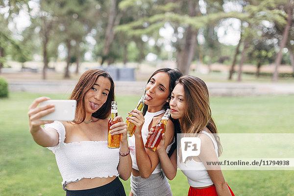 Verspielte Freunde im Park  die Bier trinken und einen Selfie nehmen