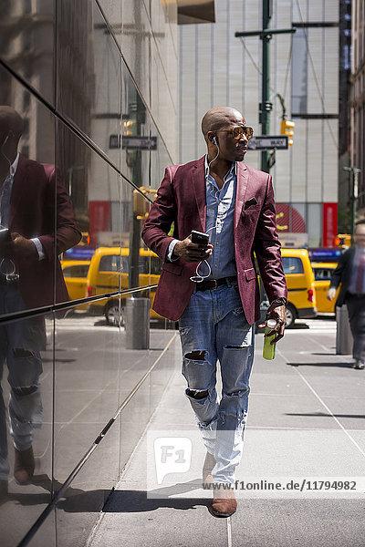 USA  New York City  Manhattan  stilvoller Geschäftsmann beim Musikhören mit Kopfhörer und Smartphone