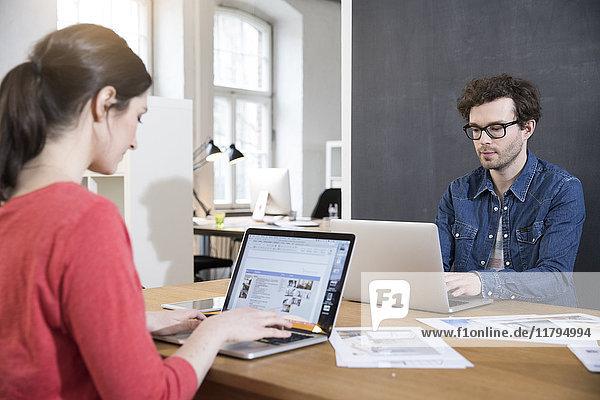 Mann und Frau mit Laptops auf dem Tisch im Büro