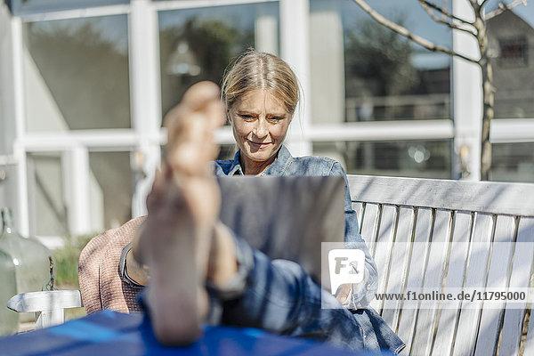 Lächelnde Frau mit Laptop im Garten