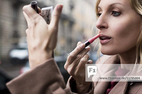 Geschäftsfrau beim Auftragen von Lippenstift im Freien