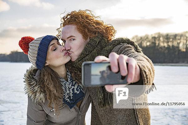 Ein Paar  das sich auf dem zugefrorenen See küsst und einen Selfie nimmt.