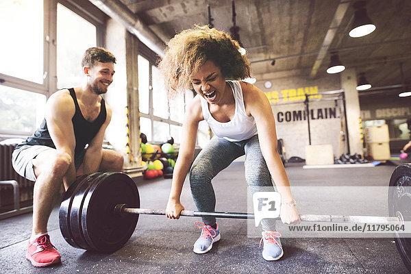 Junge Frau mit Trainingspartnerin bei der Vorbereitung zum Heben der Langhantel im Fitnessstudio