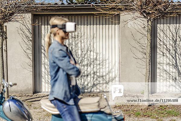 Frau sitzend rückwärts auf Oldtimer-Motorrad mit VR-Brille