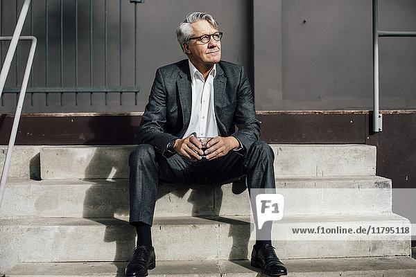 Senior Geschäftsmann auf Betontreppe sitzend
