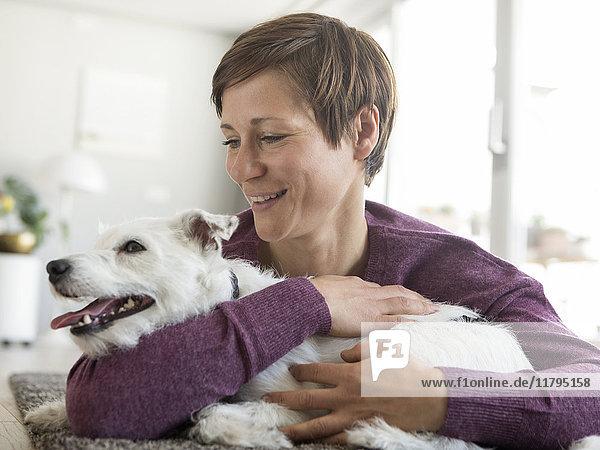 Frau umarmt ihren Hund zu Hause