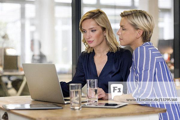 Zwei Geschäftsfrauen teilen sich einen Laptop