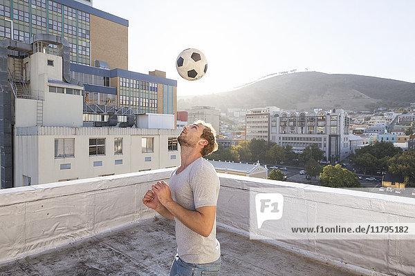 Junger Mann spielt Fußball auf der Dachterrasse