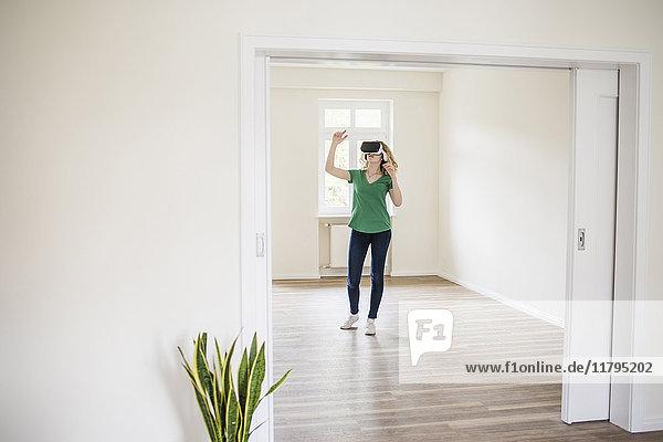 Frau in leerer Wohnung mit VR-Brille