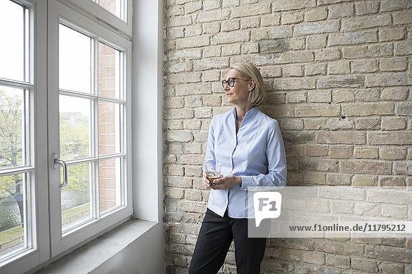 Reife Geschäftsfrau  die aus dem Fenster schaut  eine Tasse Kaffee hält