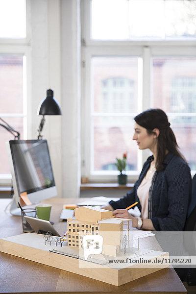 Architekturmodell und Frau am Schreibtisch im Büro