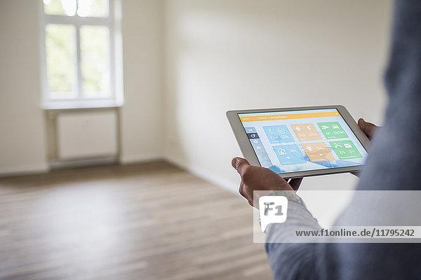 Mann im neuen Zuhause mit Tablet mit Smart Home Apps
