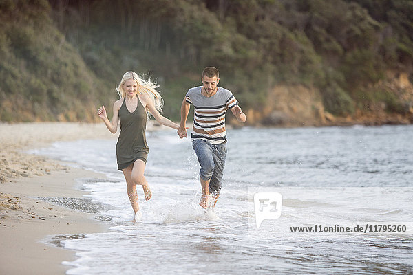 Glückliches Paar  das am Strand läuft
