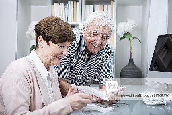 Seniorenpaar mit Rechnungen und Taschenrechner zur Kontrolle der Ausgaben
