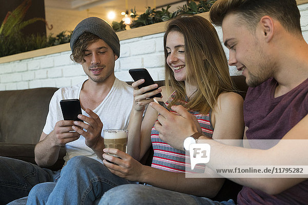 Three friends using their cell phones in a cafe
