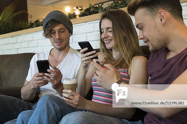 Drei Freunde  die ihre Handys in einem Café benutzen.