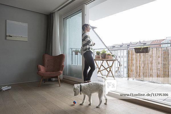 Frau steht vor offener Balkontür und schaut in die Ferne.