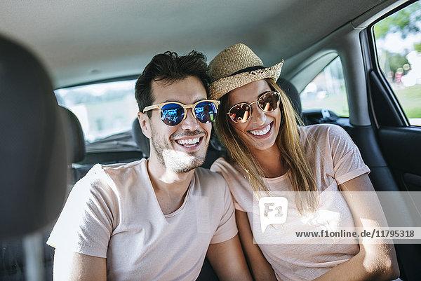 Pärchen lachend auf dem Rücksitz eines Autos