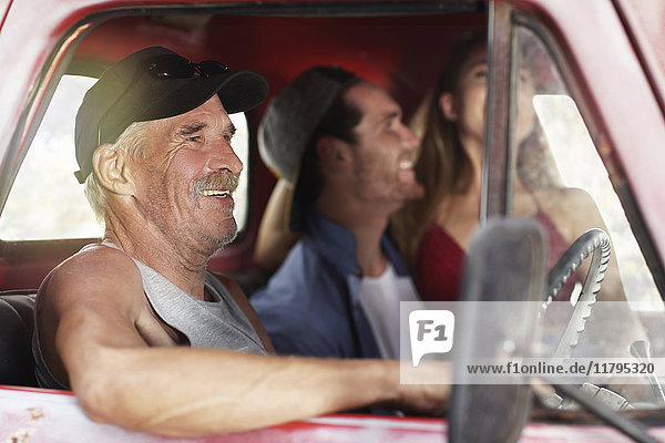 Glücklicher älterer Mann und junges Paar in einem alten Pick-Up