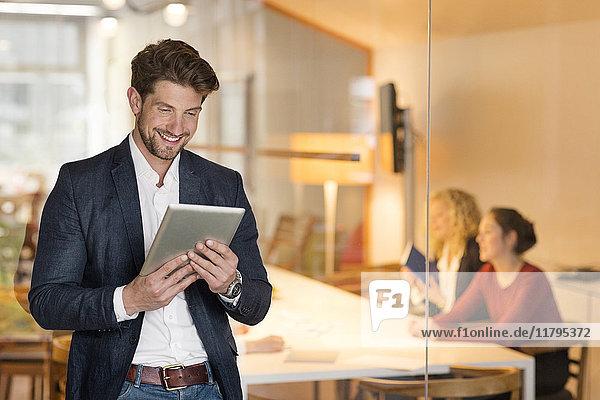 Jungunternehmer im Büro mit digitalem Tablett  mit Mitarbeitern im Hintergrund
