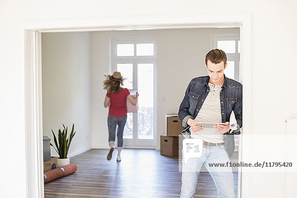 Young man in new home using tablet with woman in background carrying cardboard box