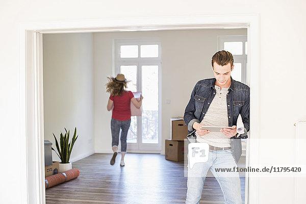 Junger Mann im neuen Zuhause mit Tablette und Frau im Hintergrund mit Kartonschachtel