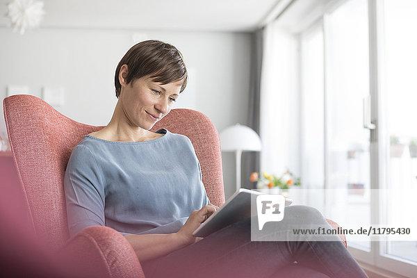 Porträt einer Frau  die zu Hause auf einem Sessel sitzt und eine Tablette benutzt.
