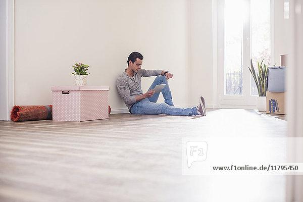 Junger Mann im neuen Zuhause sitzend auf dem Boden mit Tablette