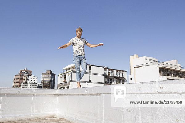 Barfüßiger Mann beim Balancieren auf der Balustrade einer Dachterrasse